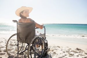accessible holidays abroad - woman on beach in a wheelchair